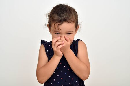 Shy cute young girl covering her mouth with hands looking at the camera 写真素材
