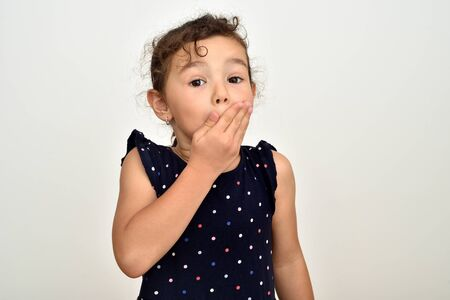 Surprised cute young girl covering her mouth with hand and looking at the camera