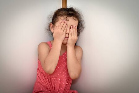 Scared and abused young girl covering her face with hands in fear of domestic violence. Stop child abuse concept.