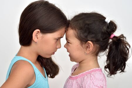 Two angry sisters standing face to face, quarreling and looking at each other