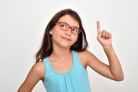 Thoughtful smiling young girl wearing glasses with index finger up having a good idea. She is  looking up.