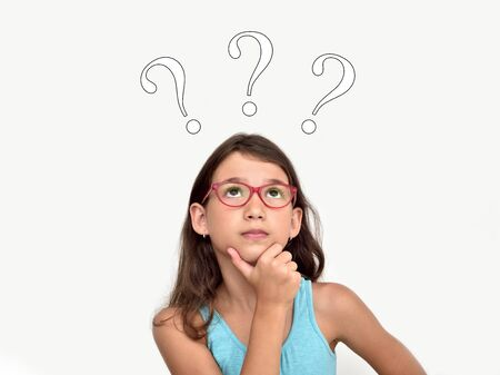 Thoughtful cute young girl wearing glasses with three question marks above her head 写真素材