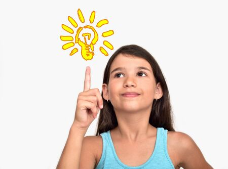 Smiling cute young girl having a good idea with light bulb above her index finger