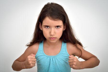 Chica joven enojada y agresiva con los puños cerrados mirando a la cámara. Concepto de infancia y expresiones.