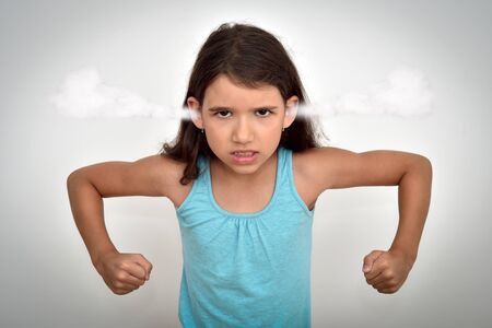 Angry and aggressive young girl with clenched teeth and fists and steam blowing out of her ears looking at the camera. Childhood and expressions concept.