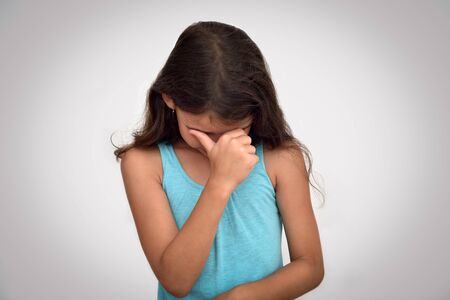 Sad, unhappy and crying young girl with hand on her face. Childhood and expressions concept.