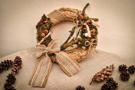 Decorated handmade Christmas wreath and pine cones on the table