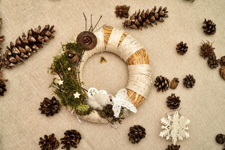 Decorated handmade Christmas wreath and pine cones on the table. High view angle.