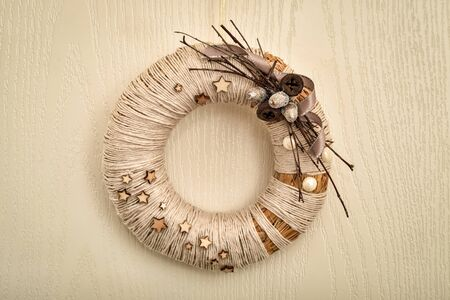 Decorated handmade Christmas wreath hanging on the rope on the wooden door 写真素材