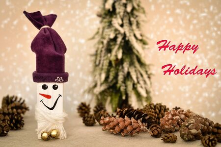 Decorated handmade wooden snowman and pine cones on the table in front of the Christmas tree and snowy background with Happy Holidays text