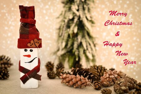 Decorated handmade wooden snowman and pine cones on the table in front of the Christmas tree and snowy background with Merry Christmas and Happy New Year text 写真素材