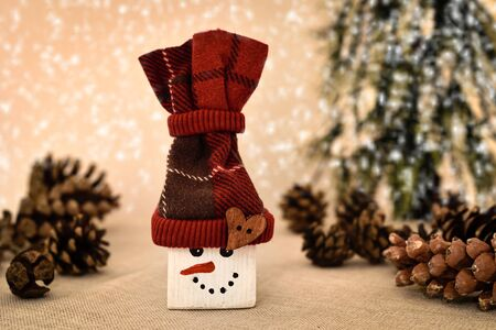 Decorated handmade wooden snowman with pine cones on the table in front of the Christmas tree and snowy background