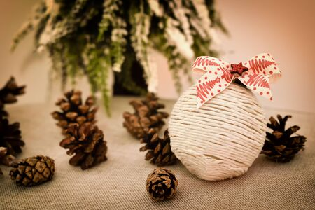 Decorated handmade Christmas bauble and pine cones on the table in front of the Christmas tree