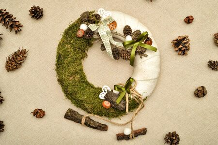 Decorated handmade Christmas wreath and pine cones on the table. Top view. Zdjęcie Seryjne