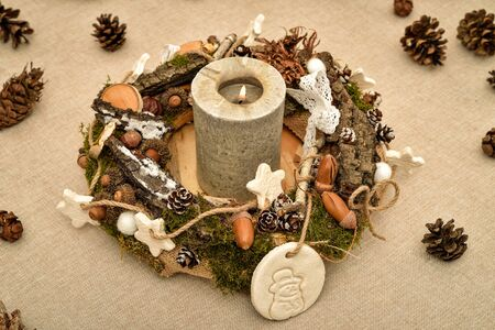 Decorated handmade Christmas wreath with candle and pine cones on the table