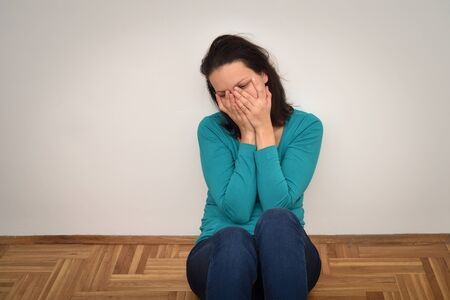 Depressed and sad woman covering her face with hands and sitting on the floor in the empty room