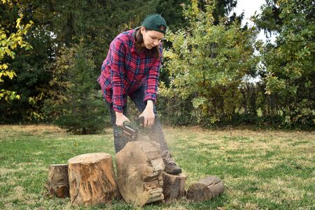 Female lumberjack with chainsaw cutting wood without safety equipment for eyes, ears and hands