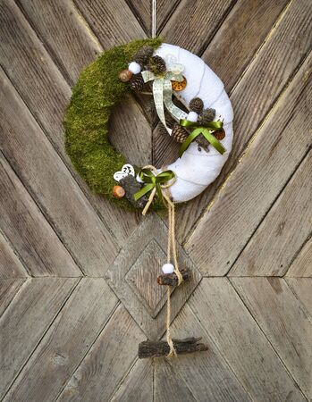 Decorated handmade Christmas wreath hanging on the rope on the rustic wooden door