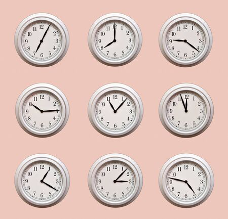 A lot of same clocks showing different times hanging on the pale orange wall