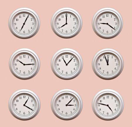 Na jasnopomarańczowej ścianie wisi wiele takich samych zegarów pokazujących różne godziny
