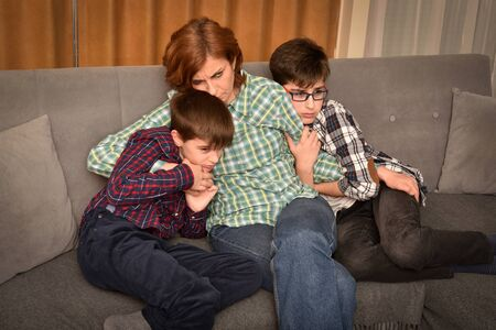 Mother and two scared sons sitting on the sofa in the living room and watching horror movie on TV