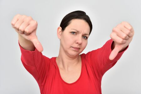 Angry and disappointed beautiful woman showing thumbs down. Selective focus. Isolated on the background.