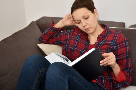 Beautiful woman wearing plaid shirt reading a book on the sofa in the living room at home 写真素材