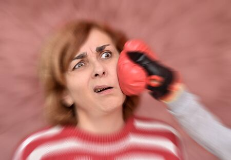 Woman getting hit in her face with red boxing glove. Radial blur effect applied around her face.