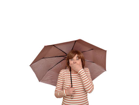 Surprised woman holding an umbrella covering her mouth with a hand and looking at camera. Isolated on white background. Stok Fotoğraf