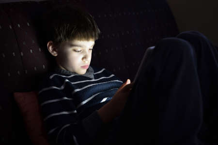 Young boy sitting on the sofa hiding in the dark room and playing on a tablet. Selective focus.