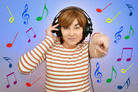 Smiling happy woman with headphones over colorful musical notes background pointing her index finger at the camera Stok Fotoğraf