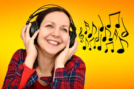 Smiling happy beautiful woman with headphones and musical notes on the orange-yellow background Stok Fotoğraf