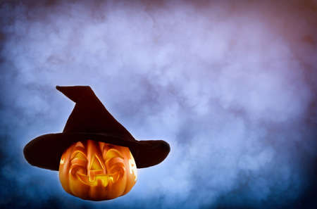 Halloween pumpkin with a black hat on the smokey background with copy space. Halloween and horror concept.