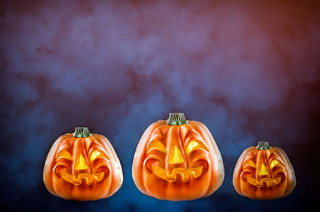 Three Halloween pumpkins on the smokey background with copy space. Halloween and horror concept.