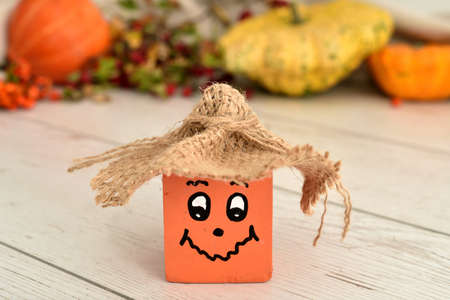 Handmade wooden cube pumpkin with funny face and hat on the rustic wooden table. Autumn fruits and plants in the blurred background. Selective focus.
