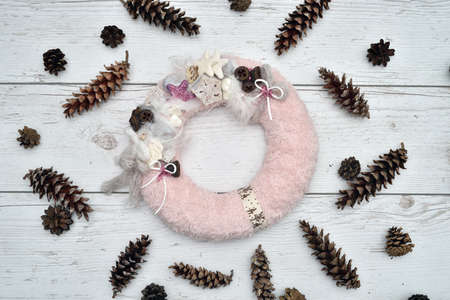 Decorated handmade Christmas wreath and pine cones on the rustic wooden table. High angle view. 版權商用圖片