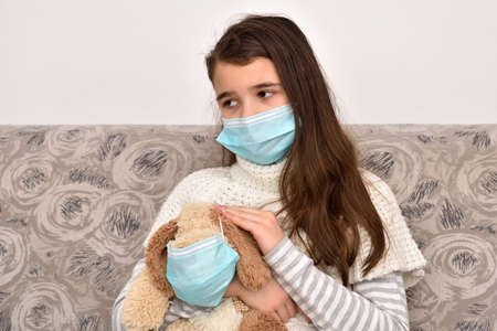 Sad and depressed young girl sitting on the sofa and holding her dog toy wearing medical protective face masks