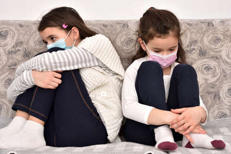 Two sad and depressed sisters sitting on the sofa with medical protective face masks Zdjęcie Seryjne