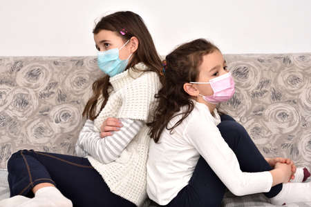 Two sad and depressed sisters sitting back to back on the sofa with medical protective face masks