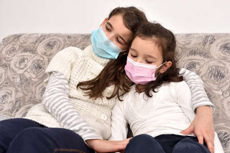 Two sad and depressed sisters sitting on the sofa with medical protective face masks. Older sister hugging her younger sister. Zdjęcie Seryjne