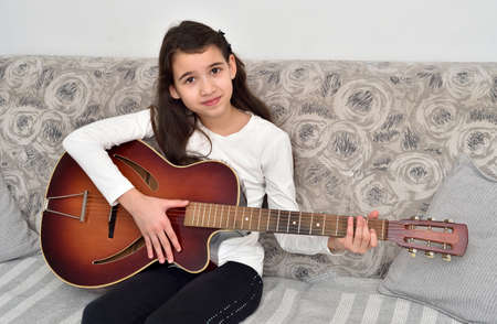 Young girl playing the guitar. Child sitting on the sofa and practicing on the vintage acoustic guitar at home. Music lesson.