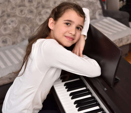 Portrait of the talented cute young girl with her piano. Child practicing on the modern electric piano at home. Music lesson. Zdjęcie Seryjne