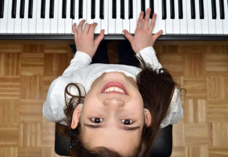 Young girl playing the piano. Child practicing on the modern electric piano at home. Music lesson. Close-up. High angle view. Zdjęcie Seryjne