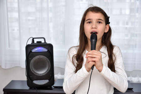 Cute young girl holding a microphone and singing at home in front of the window and loudspeaker