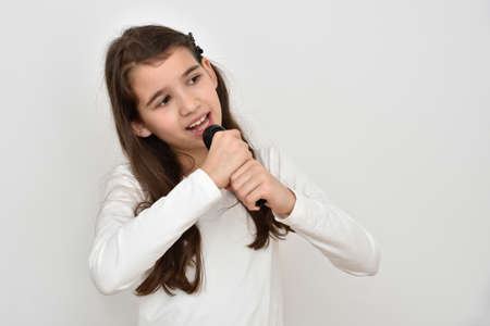 Cute young girl holding a microphone and singing. Isolated on the light gray background.