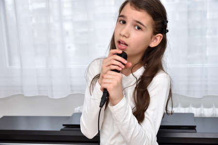 Cute young girl holding a microphone and singing at home in front of the window and electric piano
