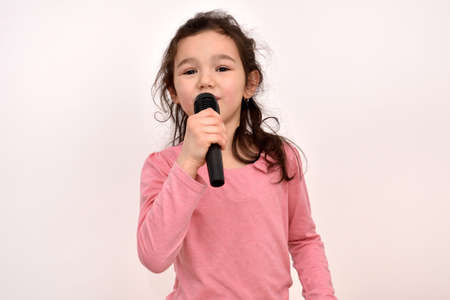Happy cute little girl singing a song on a microphone. Emotional portrait of a happy child. She has a disheveled hair. Zdjęcie Seryjne