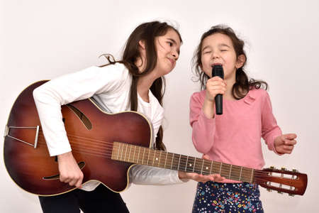 Two happy smiling sisters with a microphone and the vintage acoustic guitar fooling around and singing. Emotional portrait of happy children.