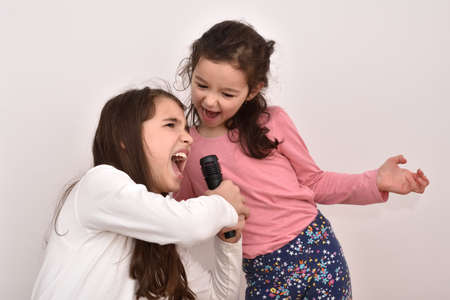 Two happy sisters fooling around and singing a song on a microphone. Emotional portrait of happy children.