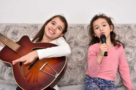Two happy smiling sisters sitting on the sofa and singing. Older sister playing a vintage acoustic guitar. Younger sister holding a microphone. Emotional portrait of happy children.